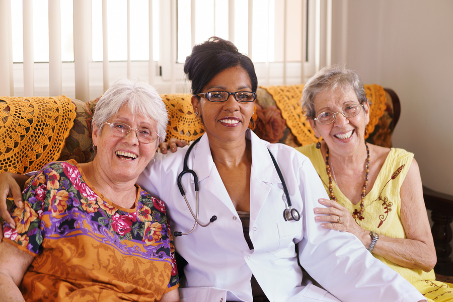 Old people in geriatric hospice: Elderly man and woman hugging an african american doctor, showing a friendly relationship between personnel and patients.